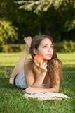 Gullig ung brunett i parkavläsningen. Royaltyfri Bild