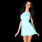 Gullig ung brunett som poserar i blåttklänning Arkivbild