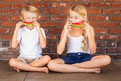 Gullig ung Caucasian pojke och flicka som tillsammans tycker om vattenmelon royaltyfria foton