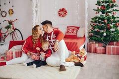 Gullig ung familj som hemma sitter på en säng arkivfoto