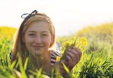 Gullig ung flicka i mitt av ett fält av blommor Royaltyfri Foto