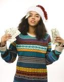 Gullig ung flicka i santas den röda hatten med isolerade pengar Arkivfoto