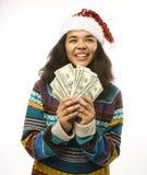 Gullig ung flicka i santas den röda hatten med pengar Royaltyfri Foto