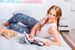 Gullig ung flicka med två flätade trådar, hemmastadd bärande pyjamas som ligger royaltyfria bilder