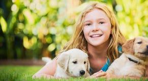 Gullig ung flicka med valpar Arkivfoton