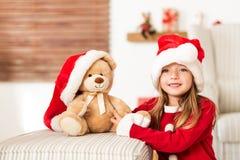 Gullig ung flicka som bär den santa hatten som rymmer hennes närvarande för jul mjuka leksaknallebjörn Lycklig unge med xmas-gåva royaltyfria bilder