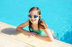 Gullig ung flicka som bär simma skyddsglasögon som har gyckel i utomhus- pöl barn som lärer bad till Unge som har gyckel med vatt royaltyfri fotografi