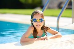 Gullig ung flicka som bär simma skyddsglasögon som har gyckel i utomhus- pöl barn som lärer bad till Unge som har gyckel med vatt royaltyfria bilder