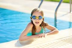 Gullig ung flicka som bär simma skyddsglasögon som har gyckel i utomhus- pöl barn som lärer bad till Unge som har gyckel med vatt royaltyfri bild