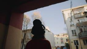 Gullig ung flicka som in går gatan mellan byggnader och lyssnande musik i hörlurar, stads- stil, tonårig stilfull hipster