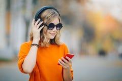 Gullig ung flicka som går ner den gamla stadsgatan och lyssnande musik i hörlurar, stads- stil, tonårig håll för stilfull hipster arkivfoto