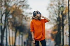 Gullig ung flicka som in går ner den gamla stadsgatan och lyssnande musik i hörlurar, stads- stil, tonårig stilfull hipster royaltyfri bild
