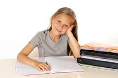 Gullig ung flicka som hemma studerar på ett skrivbord med en studiebok på en vit bakgrund fotografering för bildbyråer