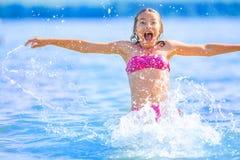 Gullig ung flicka som spelar i havet Den lyckliga pre-tonåriga flickan tycker om sommarvatten och semestrar i feriedestinationer Royaltyfri Bild
