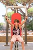 Gullig ung flicka som utomhus övar övrekroppen på idrottshallmaskinen Royaltyfri Bild