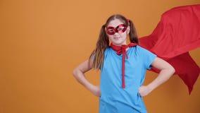 Gullig ung flickaleksuperhero på en orange bakgrundsbakgrund stock video