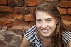 Gullig ung flickanärbildstående nära en tegelstenvägg Lycka Arkivbild
