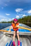 Gullig ung flickarodd en roddbåt på en sjö med blå sommarhimmel i bakgrunden arkivbilder