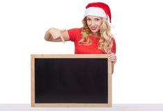 Gullig ung kvinna i framsida för Santa Claus hattnederlag bak tomt vitt bräde Arkivfoto
