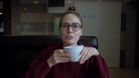 Gullig ung kvinna i glasögon som sitter i kafét och talar till någon