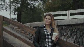 Gullig ung kvinna med en utomhus- kopp kaffe Nätt flicka som tycker om hennes morgon lager videofilmer