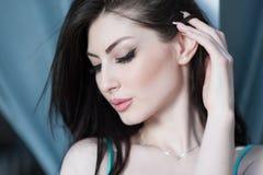 Gullig ung kvinna med stängda ögon som försiktigt trycker på hennes hår med fingrar Royaltyfri Bild
