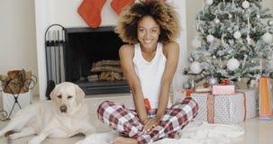 Gullig ung kvinna och hennes hund på jul Royaltyfri Bild