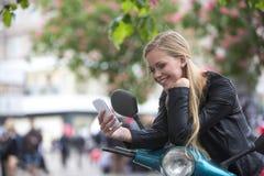 Gullig ung kvinna på en sparkcykel som skrattar se telefonen Royaltyfri Fotografi