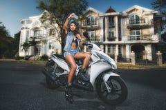 Gullig ung kvinna på vit sparkcykeldanandeselfie mot stadshimmel Royaltyfria Foton