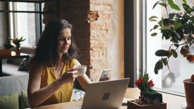 Gullig ung kvinna som dricker te genom att använda smartphonen i kafét som kopplar av att le stock video