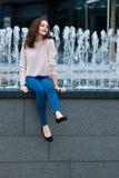 Gullig ung kvinna som har gyckel bredvid springbrunnen på gatan av staden Royaltyfri Fotografi