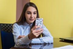 Gullig ung kvinna som pratar med vännen eller direktanslutet shoppar med smartphonen Härlig telefonräkning med rosa blommor Arkivbild