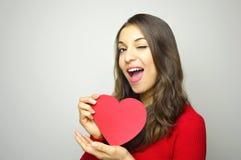 Gullig ung kvinna som rymmer en pappers- hjärtablinkning och leende på kameran på grå bakgrund Begrepp för dag för valentin` s Arkivbild