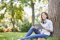 Gullig ung kvinna som ser som ett studentsammanträde i en parkera på gräset under ett träd arkivfoto