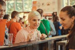 Gullig ung kvinna som talar med bartendern om klappöl i upptagen bar Royaltyfri Foto
