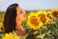 Gullig ung kvinna som tycker om solrosor fotografering för bildbyråer
