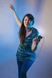 Gullig ung kvinnlig utfrågningmusik från en spelare mp3 Royaltyfria Foton