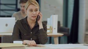 Gullig ung kvinnlig vuxen människa på telefonen, medan arbeta på skrivbordet arkivfilmer
