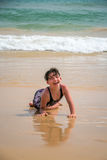 Gullig ung liten flicka som skrattar att lägga i en baddräkt i sanden på en strand Arkivbild