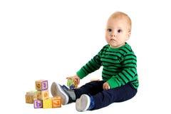 Gullig ung litet barnpojke som spelar med alfabetkvarter Royaltyfri Bild