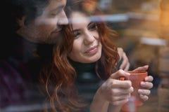 Gullig ung man och kvinna som omfamnar nära fönster royaltyfri foto