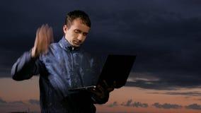 Gullig ung man som arbetar på bärbara datorn på solnedgången på fältet Härlig himmel på en bakgrund arkivfilmer