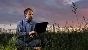 Gullig ung man som arbetar på bärbara datorn på solnedgången på fältet Härlig himmel på en bakgrund lager videofilmer