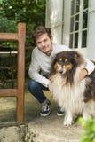 Gullig ung man som utomhus knäfaller med den håriga colliehunden Royaltyfria Foton