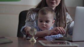 Gullig ung moder f?r st?ende och liten son som inomhus placeras med en b?rbar dator p? tabellen Upptagen ung moder som hemma arbe lager videofilmer