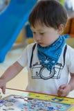 Gullig ung pojke som gör ett pussel Arkivfoto