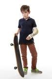 Gullig ung pojke som rymmer en skateboard Arkivbilder