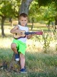 Gullig ung pojke som spelar gitarren nära trädet Arkivbilder