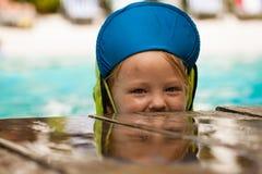Gullig ung pojke som spelar i vatten Arkivfoto