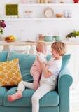 Gullig ung pojke som spelar med det lilla spädbarnet för att behandla som ett barn systern hemma på soffan arkivfoton